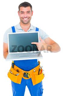 Happy repairman pointing at laptop