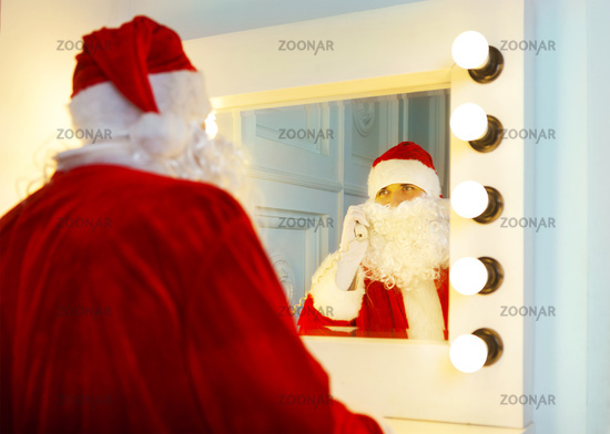 Photo of happy Santa Claus talking to the phone