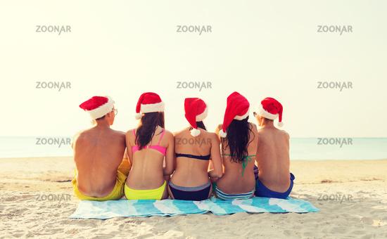 group of friends in santa helper hats on beach