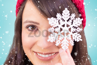 Composite image of festive brunette holding snowflake decoration