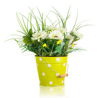 Bouquet from artificial flowers arrangement centerpiece in yellow metal bucket.