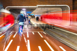 Pedestrians and cyclists at entrance to tunnel under Central Station, Amsterdam, Netherlands, Europe