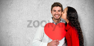 Composite image of man holding paper heart and being kissed by girlfriend