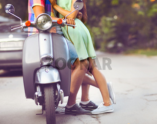 Young happy couple near the old retro scooter in a city street. Close up