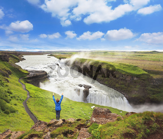Delighted woman tourist on the shore of the waterfall. Gyullfoss, Iceland