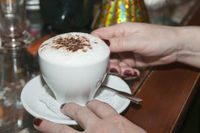 Serving a cup of cappuccino