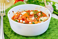 Shrimp and tomatoes with feta in white bowl on board