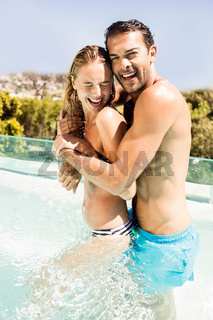 Happy couple in the pool embracing