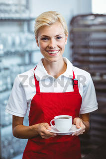 Pretty barista holding a cup of coffee
