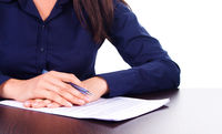 Woman signs a contract on a table, isolated over white