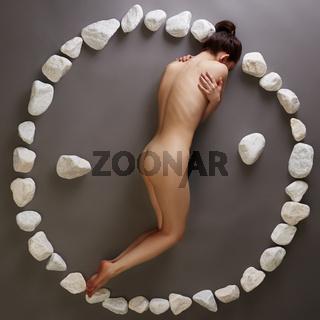 Yin-yang. Nude woman posing with stones