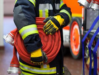 Feuerwehrmann im Einsatz mit Wasserschlauch