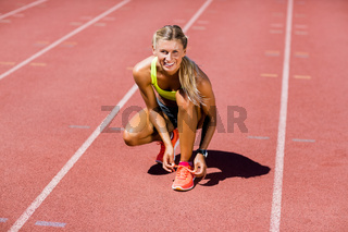 Portrait of female athlete tying her shoe laces on running track
