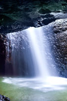 Waterfall blurred and falling down in a dark stone cave