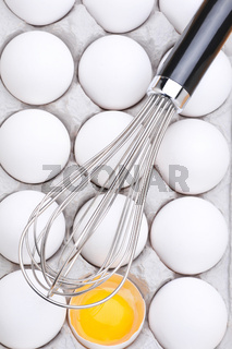 Whisk Laying Across a Carton of Eggs