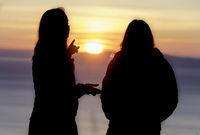 Silhouette of girls watching sunset