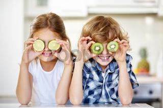 Zwei Kinder verstecken Gesicht hinter Kiwi