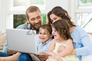 Parents and kids using laptop in living room