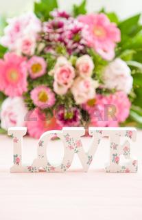LOVE vor buntem Blumenstrauss