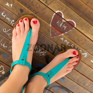 Female feet wearing turquoise sandals.