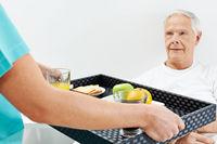 Senior im Pflegeheim bekommt Frühstück ans Bett