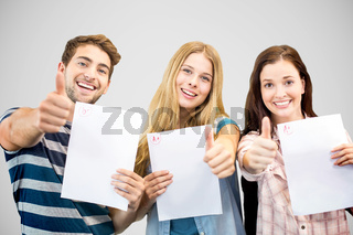 Composite image of students holding up exam and doing thumbs up