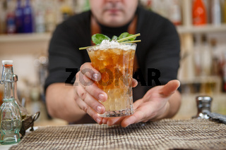 Bartender is standing in pubб holding cocktail and giving glass forward. Focus on beverage.
