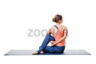 Woman practices yoga asana  Ardha matsyendrasana
