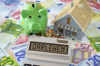 Das Wort Darlehen auf Display von Taschenrechner und Sparschwein