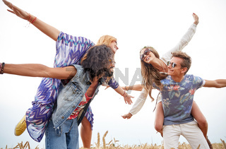 happy hippie friends having fun on cereal field