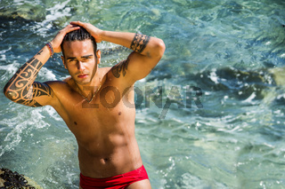 Young man standing in water by sea or ocean shore,