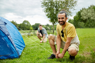 smiling friends setting up tent outdoors