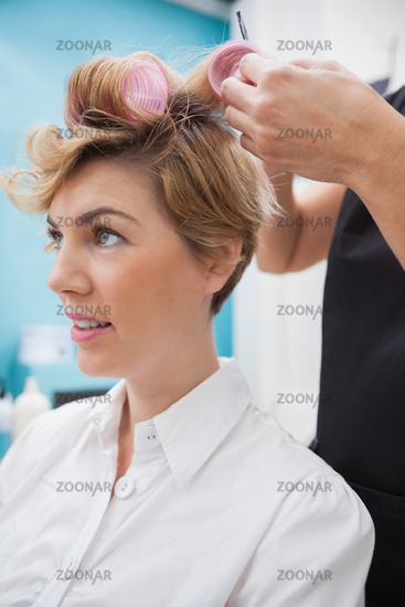 Hairdresser setting curlers in hair