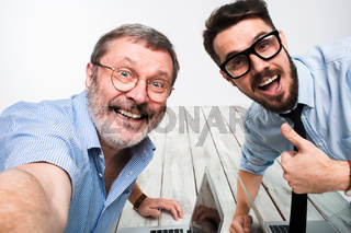 Two colleagues  taking the picture to them self sitting in  office