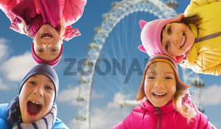 happy little children faces over ferry wheel