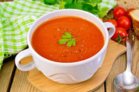 Soup tomato in bowl with spoon on board
