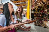 Two lovely girls playing shooting games and having fun at German funfair Oktoberfest. Wearing traditional Dirndl dresses.