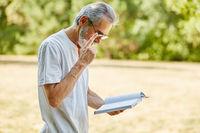 Alter Mann liest in einem Buch