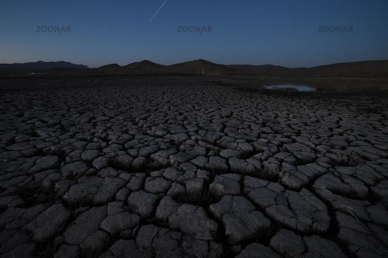 Cracked soil landscape after sunset