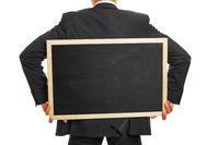 Mann trägt leere Tafel auf Rücken
