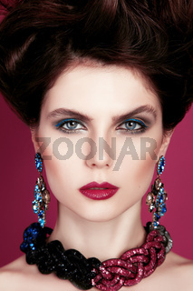 Closeup portrait with deep blue eye, creative makeup and pink purple accessories