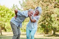 Frau hilft altem Mann mit Rückenschmerzen