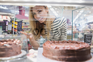 Portrait of woman looking at desserts shelf