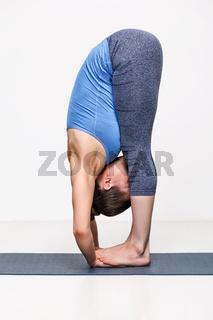 Sporty fit woman in yoga asana Padahastasana