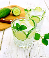 Lemonade with cucumber and mint in two glassful on light board