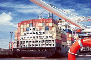 Das Heck eines großen, beladenen Containerschiffs im Hafen