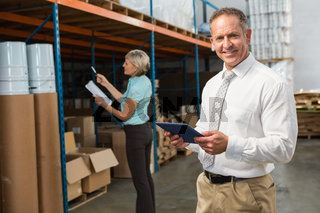 Smiling warehouse manager using tablet pc