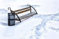 Lonely bench in winter park and footpath in snow