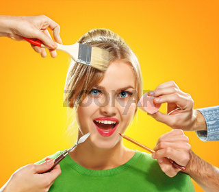 The hands of visagists doing make-up young woman
