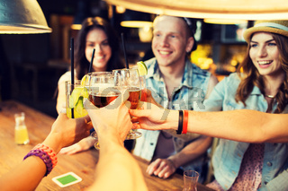 happy friends clinking glasses at bar or pub